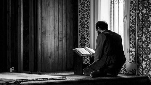 モスクでコーランを読む男性