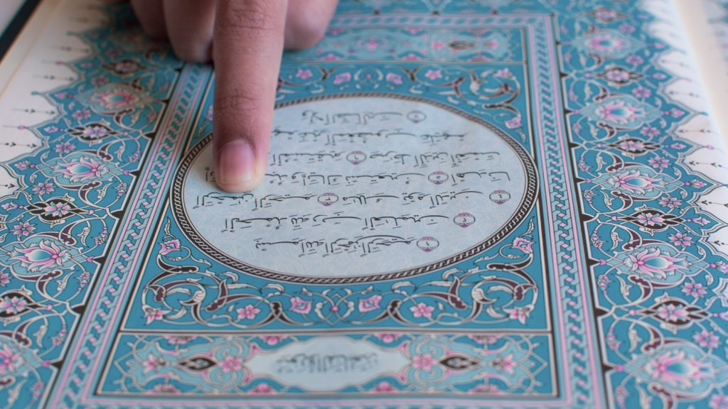コーランに書かれたアラビア文字を指差す